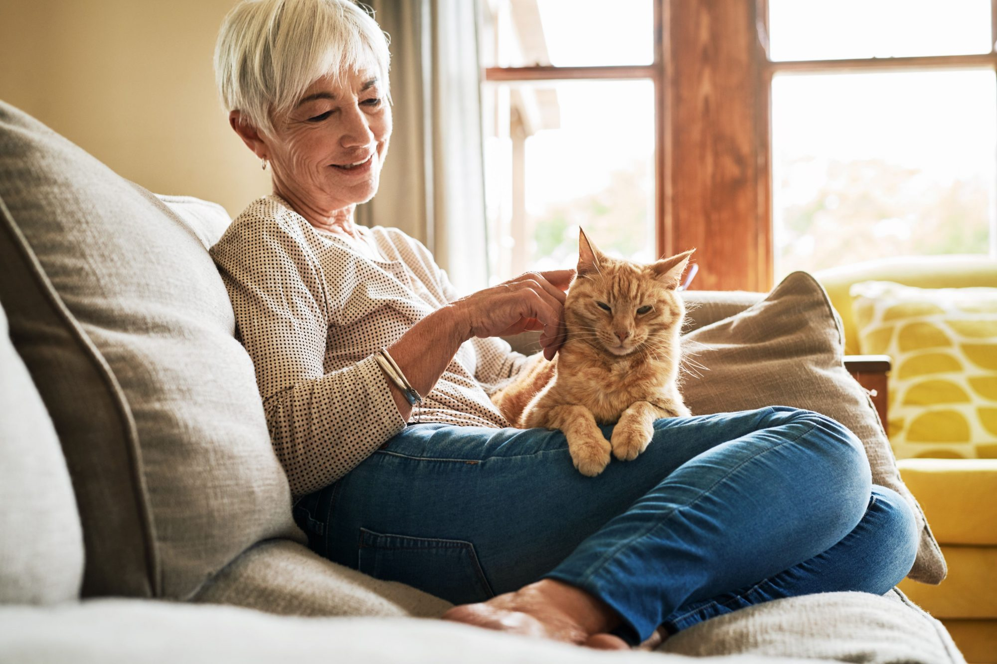 An older woman sits with her cat on her lap.